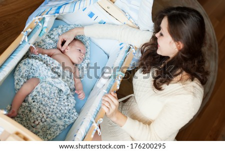 Portrait of young mother sitting near the newborn baby in cradle  - stock photo