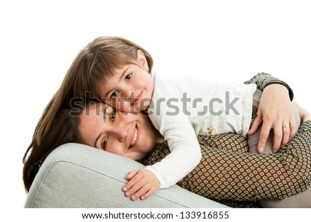 Portrait of young mother with daughter on couch.Isolated. - stock photo
