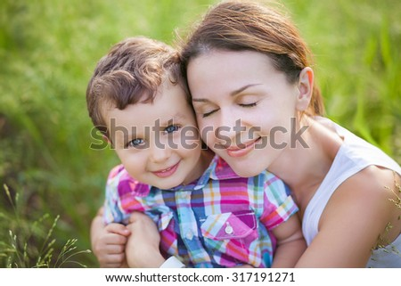 Portrait of young mother with her son on a field