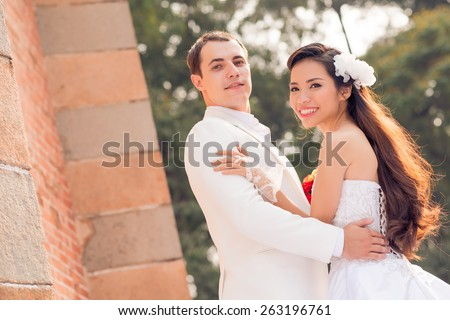 Portrait of young multi-ethnic wedding couple smiling and looking at the camera - stock photo