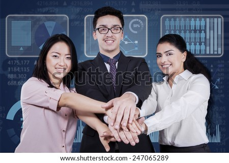 Portrait of young multicultural businesspeople smiling at the camera while joining hands - stock photo