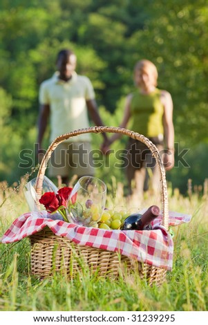 portrait of young multiethnic couple holding hands and picnicking in park - stock photo
