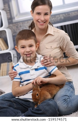 Portrait of young mum and cute son with pet rabbit in living room.