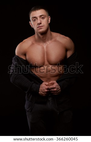 Portrait of young muscular bodybuilder looking at camera on black background. Studio shot