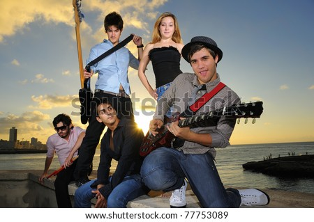 Portrait of young musical band with 4 boys and a girl posing outdoors at sunset with instruments - stock photo