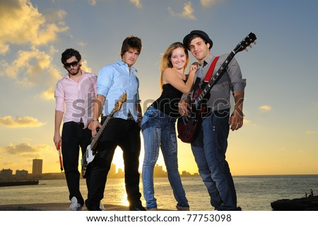 Portrait of young musical band with 3 boys and a girl posing outdoors at sunset with instruments - stock photo