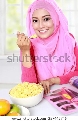portrait of young muslim woman enjoy eating a cereal while reading a magazine - stock photo
