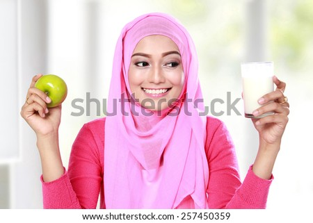 portrait of young muslim woman holding an apple and a glass of milk - stock photo