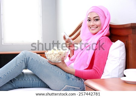 portrait of young muslim woman holding mobilephone and a bowl of popcorn on bed - stock photo