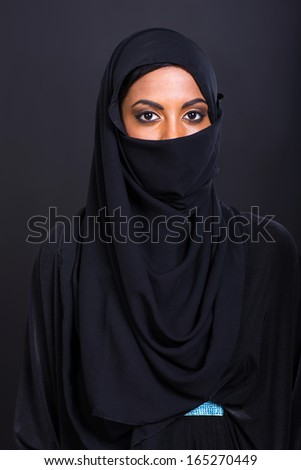 portrait of young muslim woman on black - stock photo