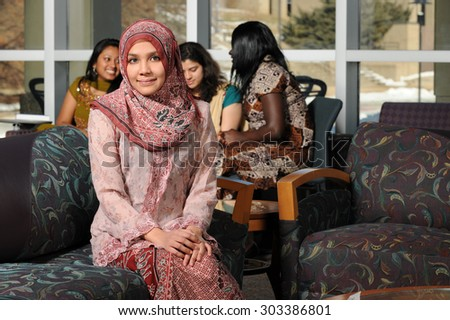 Portrait of young Muslim woman with headscarf inside college building on campus - stock photo