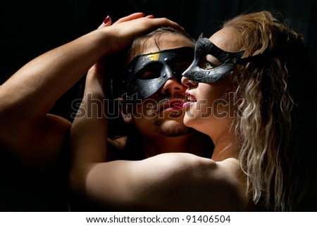 Portrait of young mysterious couple in a Venetian mask during sexual foreplay - stock photo
