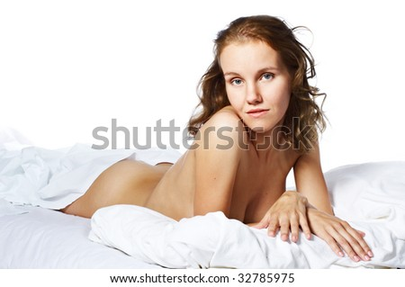 Portrait of young naked woman lying on bed - stock photo