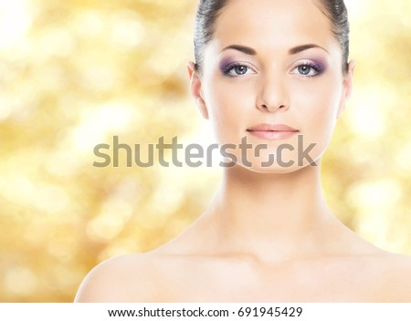 Portrait of young, natural and healthy woman over yellow autumn background. Healthcare, spa, makeup and face lifting concept.