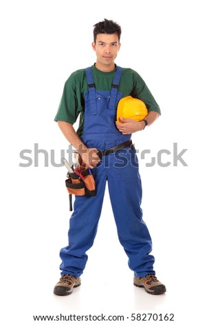 Portrait of young Nepalese attractive carpenter wearing a blue overall, tool belt and holding a  yellow helmet . Studio shot. White background. - stock photo