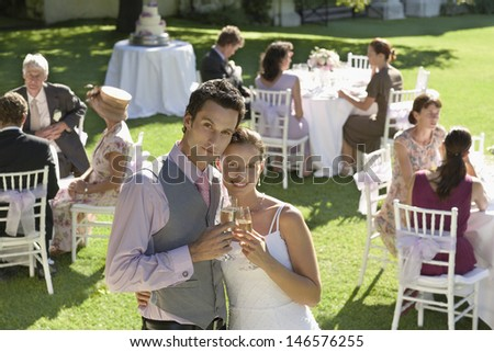 Portrait of young newlywed couple toasting champagne while wedding guests sitting in garden - stock photo