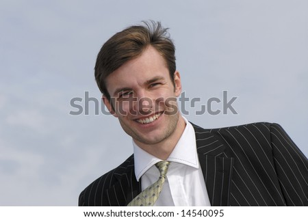 Portrait of  young nice businessman on background of  sky,  close up