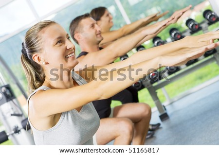 Portrait of young nice people  getting busy in gym - stock photo