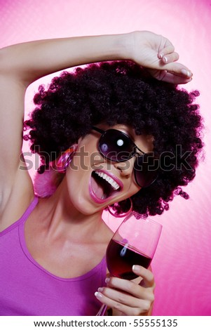 Portrait of young nice woman with glass of wine on pink back - stock photo