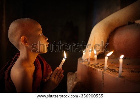 Portrait of young novice monk praying with candlelight inside a Buddhist temple, low light setting, Bagan, Myanmar. - stock photo