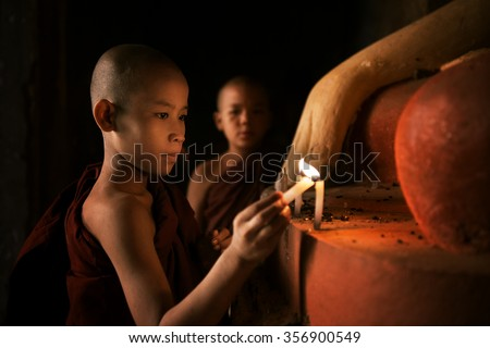 Portrait of young novice monks lighting up candlelight inside a Buddhist temple, low light setting, Bagan, Myanmar. - stock photo