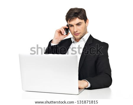 Portrait of young office worker with  laptop speaks by mobile phone sitting on the table  isolated on white. - stock photo