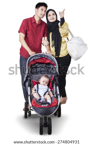 Portrait of young parents pushing their baby in the stroller while looking at something, isolated on white background - stock photo