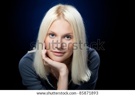 Portrait of young pensive female looking at camera over dark blue background, shallow deep of field - stock photo