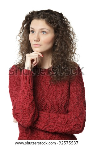 Portrait of young pensive female standing with folded hands and her hand on the chin looking sideways, over white background - stock photo