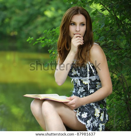 Portrait of young pensive girl holding book, wearing black dress at summer green park. - stock photo