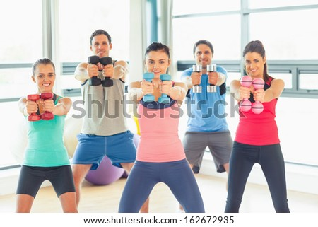 Portrait of young people lifting dumbbell weights with trainer in a bright gym - stock photo