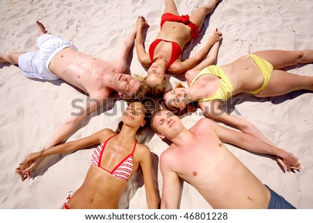 Portrait of young people lying in the circle and holding by hands each other - stock photo