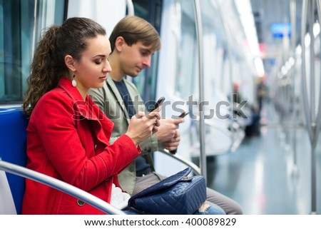 Portrait of young people reading news with mobile phones underground