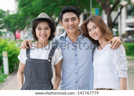 Portrait of young people standing together outside - stock photo