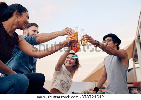 Portrait of young people toasting cocktails during a party. Four young friends enjoying in a party. Young man and woman hanging out together. - stock photo