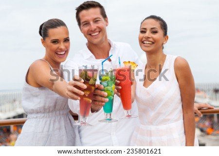 portrait of young people toasting with cocktail drinks on a cruise ship - stock photo