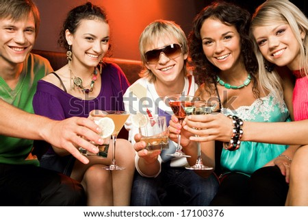 Portrait of young people touching the glasses with each other in the nightclub