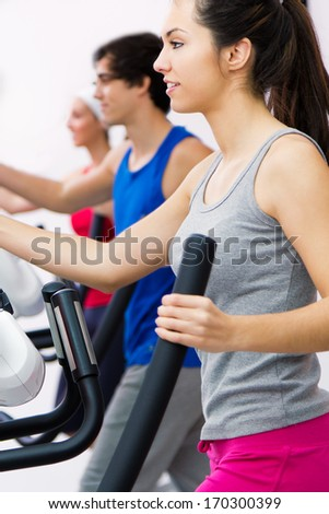 Portrait of young people with elliptic machine in the gym - stock photo