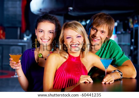 Portrait of young people with martini glasses laughing in the nightclub - stock photo