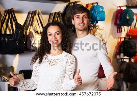 Portrait of young positive customers in store of hanbags