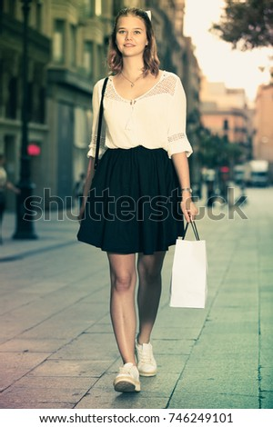 Portrait of young positive female walking at the modern street