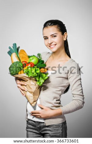 Portrait of young positive pregnant woman standing against grey background. Woman looking at camera and holding package with fresh vegetables and bread. Concept for healthy food - stock photo