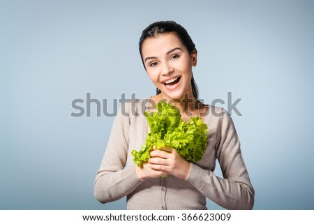 Portrait of young positive woman standing against grey background. Woman looking at camera and holding fresh sheaf of lettuce - stock photo