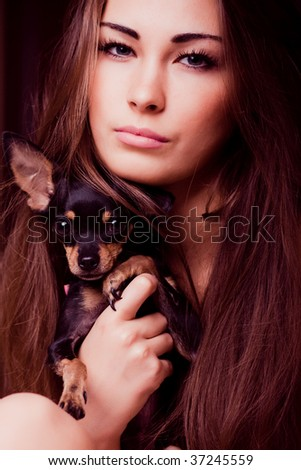 Portrait of young pratty woman holding dog in her hands - stock photo