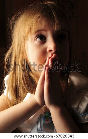 Portrait of young praying girl sitting in comfortable armchair in dark room with lightning lantern - stock photo