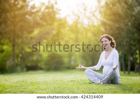 Portrait of young pregnant model working out in park. Smiling future mom expecting child sitting cross-legged on meditation session and looking at camera. Prenatal Yoga. Copy space for text message - stock photo