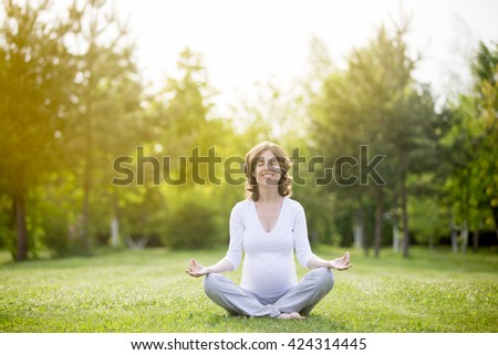 Portrait of young pregnant model working out in park. Smiling future mom expecting child sitting cross-legged and meditating with closed eyes outdoors. Prenatal Yoga. Copy space - stock photo