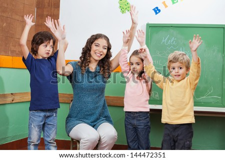 Portrait of young preschool teacher and children with hands raised in classroom - stock photo