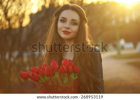 POrtrait of young pretty beautiful smiling girl with long dark hair with red tulips bouquet posing at sunset