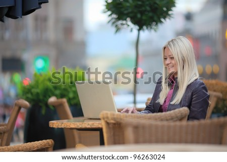 Portrait of young pretty blonde woman sitting in street cafe with her laptop, typing and smiling - stock photo